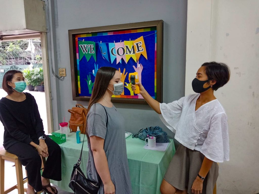 Michelle Ford gets a temperature check on her way to worship with the Somprasong 4 Church of Christ in Bangkok.