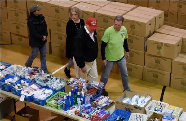 President Donald Trump walks with Laura Bates, Rick Gilbert and Tennessee First Lady Maria Lee, left, at a supply distribution center at Jefferson Ave. Church of Christ in Cookeville, Tenn., during his visit to tornado-ravaged areas in the state.