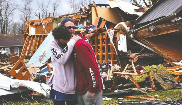 Deanna Herald Speck and husband, Tony, of Cookeville, stand near what is left of her parents' house. Dwight and Sue Herald live in the Locust Grove community. The Heralds said the house started to shake and fell as they reached safety in the stairwell.