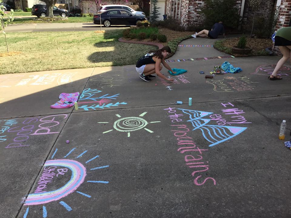 A group of young ladies from the Broken Arrow Church of Christ use chalk to draw pictures and write encouraging notes on the Pyles' driveway.