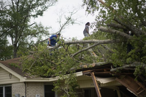 One Kingdom volunteers work of the roof of a house after tornadoes hit the Monroe, La., area.