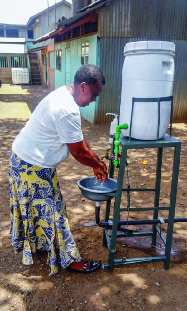 A woman in Kenya uses a pedal-operated hand-washing station designed by minister Nyabuto Marube. The minister buys water containers from families who use the money to purchase food.