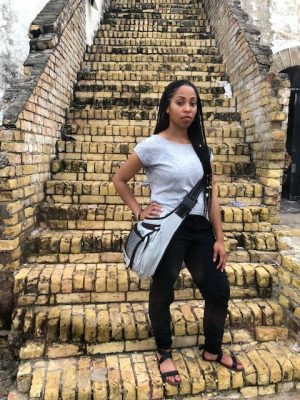 Ashley Moneet Williams stands on the steps of the Cape Coast Castle in the African nation of Ghana.