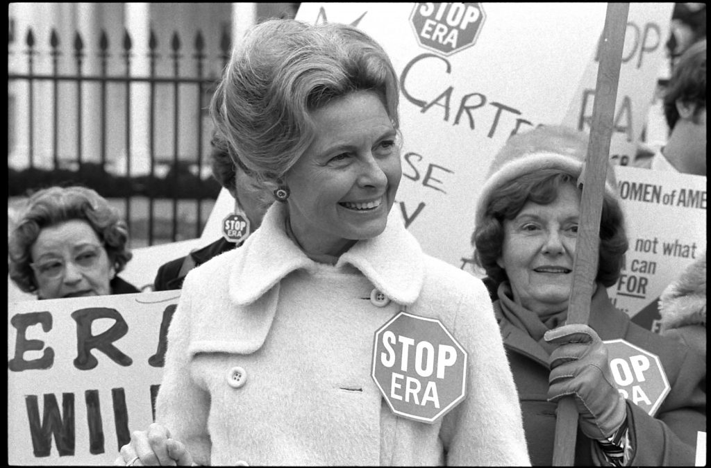 "Activist Phyllis Schlafly wearing a ""Stop ERA"" badge, demonstrating with other women against the Equal Rights Amendment in front of the White House, Washington, D.C., February 4, 1977."