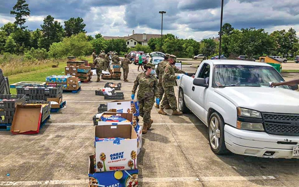 Texas National Guard members help distribute food at Grace Crossing, a Community Church of Christ in Conroe, Texas.