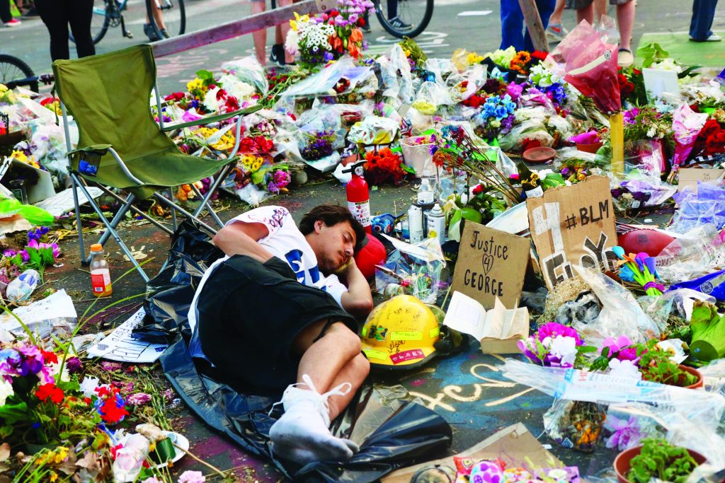 A man rests amid flowers and memorials for George Floyd during protests in Minneapolis. Floyd, 46, was accused of trying to pass a fake $20 bill. He died in police custody.