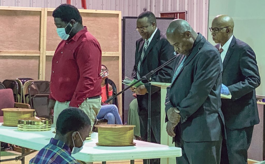 Members of the Lewis Street Church of Christ pray during the Lord's Supper. The Little Rock, Ark., congregation meets in its gym under strict social distancing guidelines, minister Jameel Robinson said.