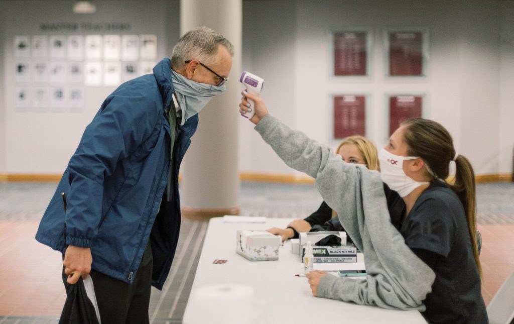 At Oklahoma Christian University, Jeff McCormack, dean of the College of Natural and Health Sciences, gets a temperature check before starting work.