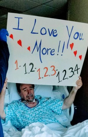 Marty Neal holds a sign up in a hospital window showing his family which room he was in.