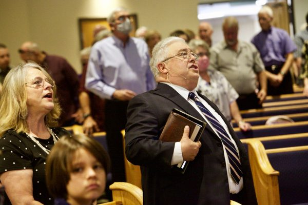 Minister Britt Farmer and his wife, Lisa, sing during Sunday's service.