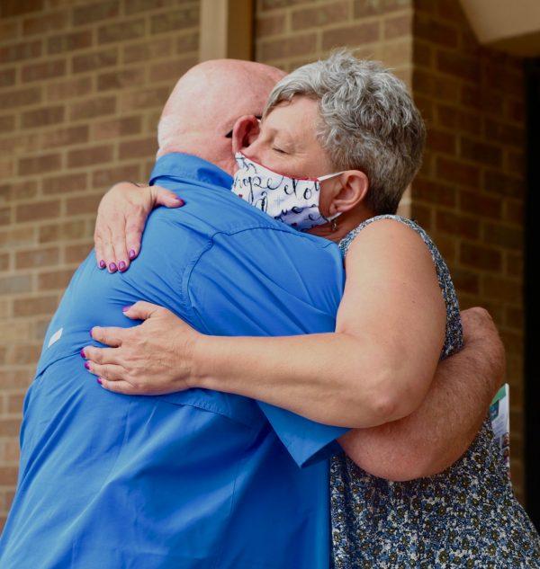 Hugh Galyean hugs Glenda White, whose husband, Richard White, 67, died in the shooting.