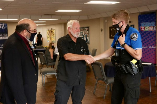 Jack Wilson, the church security team leader who killed the gunman, shakes hands Sunday with a White Settlement police officer. At right is church elder John Robertson.