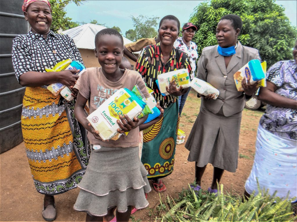 With street markets closed, members of the Oyaro Church of Christ in Kenya receive food aid from Healing Hands International. The church has many orphans and widows due to HIV/AIDS.
