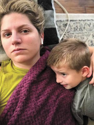"""""""Really think about where you go today and who you'll be around. And wear a mask when you can,"""" Laura Akins wrote in a July 4 social media post. """"I have COVID and it hurts really bad."""" In this photo she and her son, Wiley, rest and recuperate."""