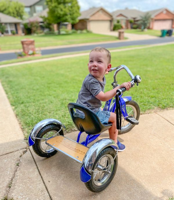 Bennett Ross, 2, rides a tricycle while playing outside with his grandmother.