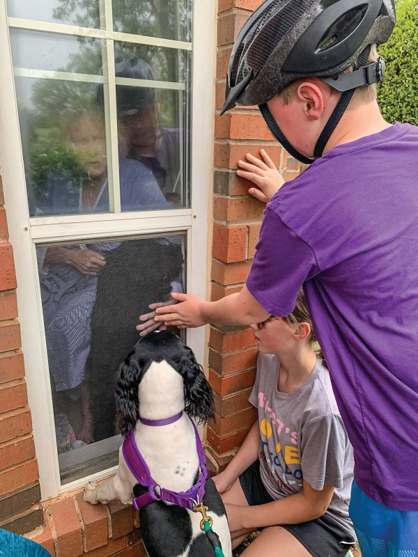 "Knox Watson and his grandmother, Judy Forrester, press their hands against a window at Tealridge, an independent living facility in Oklahoma City, as they say goodbye. Watson's sister, Nora, and their dog, Mae, also came to see Forrester, 72. ""She hasn't been able to hug them since March,"" said Forrester's daughter, Amanda Watson, events coordinator for Oklahoma Christian University. ""She is lonely but doing good."""