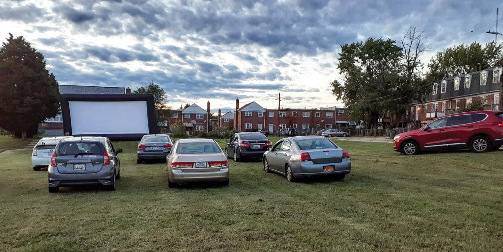 "Motorists park on a grassy lot of the Inner City Church of Christ in Baltimore to watch a drive-in showing of the superhero movie ""Black Panther."""