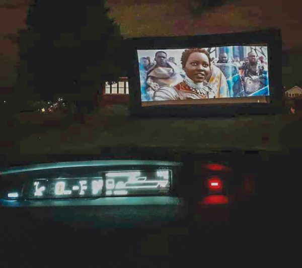 """Black Panther,"" starring the late actor Chadwick Boseman, plays on an outdoor screen during a Movie Night sponsored by the Inner City Church of Christ."