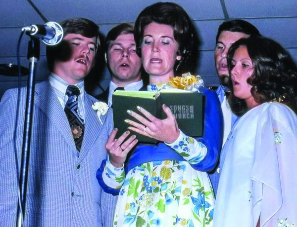 "Students and wives sing at a White's Ferry Road School of Preaching banquet, using a ""Songs of the Church"" songbook published by elder Alton Howard's company."