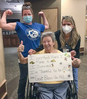 "After recovering from COVID-19, a resident of the Church of Christ Care Center in Michigan celebrates with staffers and holds up a sign that reads ""I survived."" and celebrates with staffers after recovering from."