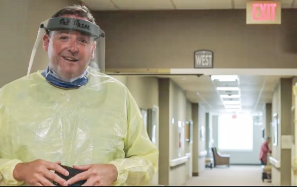 Decked out in personal protective equipment, Mike Mazza narrates a video at Christian Care Communities & Services' Mesquite, Texas, campus.