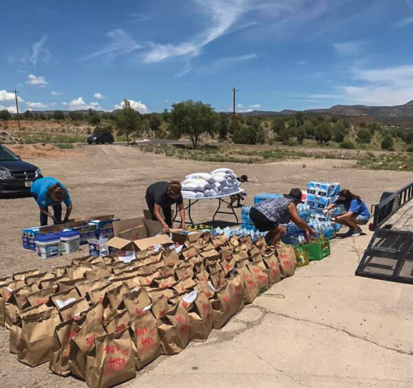 At the Fort Apache Reservation in Arizona, church members prepare for a drive-through giveaway of bags with relief supplies and encouraging notes.