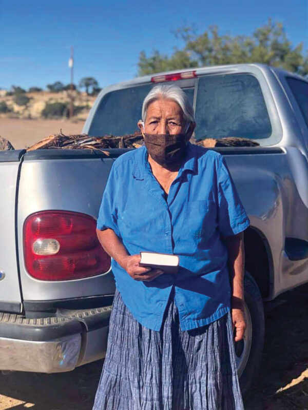 A grandmother of members of the Burnt Corn Mountain Church of Christ in Pinion, Ariz., receives a Bible and firewood from the Salt River church for the winter.
