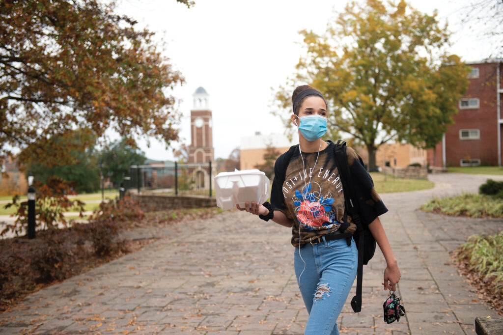To-go lunch in hand, Brooke Mefford walks alone on the campus of Freed-Hardeman University in Henderson, Tenn.