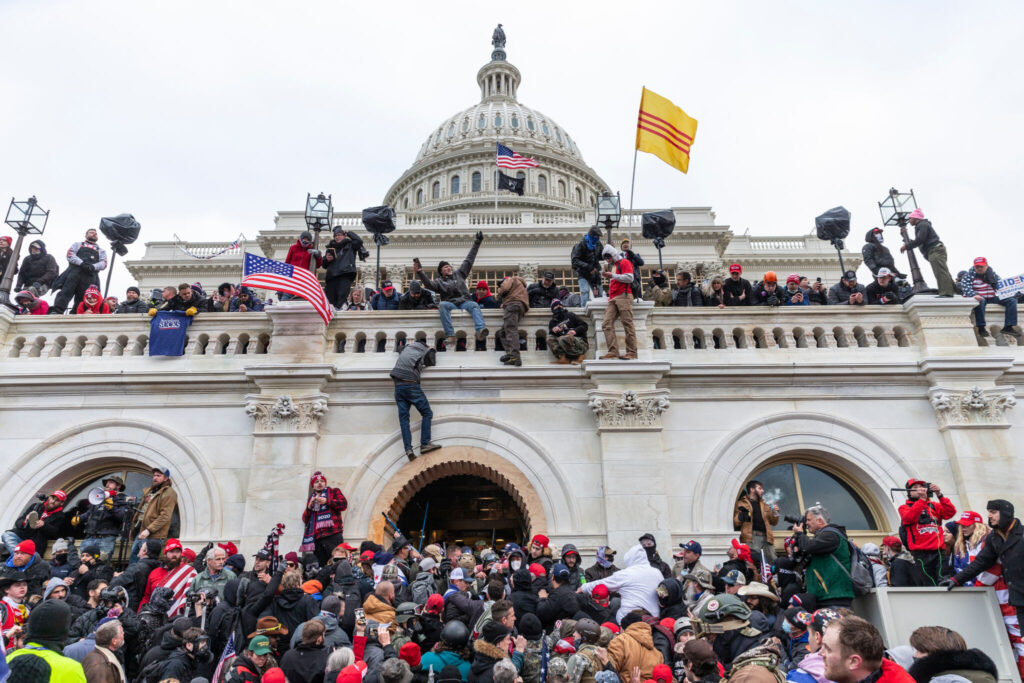 Protesters wave flags and climb the walls of the U.S. Capitol building on Jan. 6.
