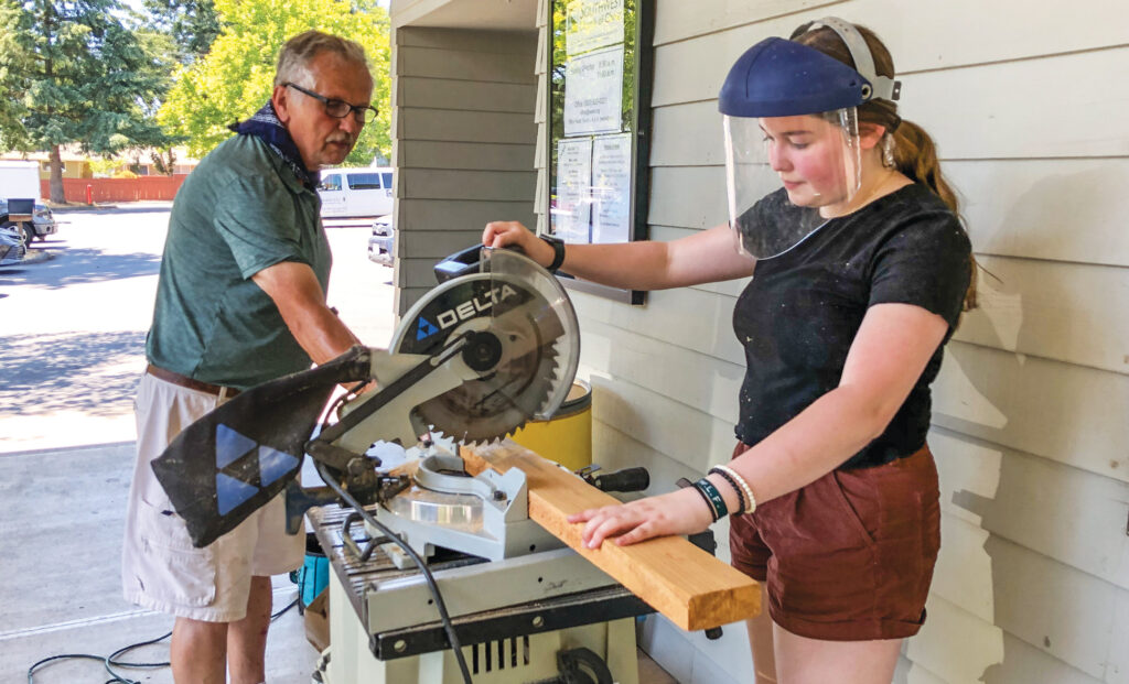 "Madeline Lewis cuts lumber during ""Mission Stay"" by the Southwest Church of Christ in Tigard, Ore. The youth group worked on projects close to home."