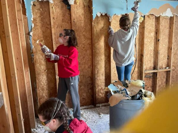 Members of the RiverHawks for Christ ministry remove flood-damaged boards from a home in eastern Kentucky.