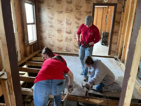 Members of the RiverHawks for Christ ministry remove floorboards from a flood-damaged home in eastern Kentucky.