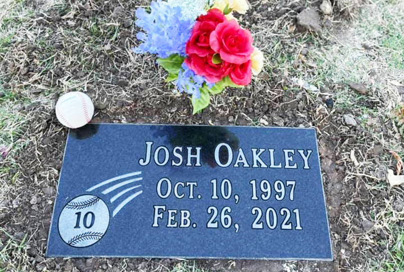 A temporary headstone, baseball and flowers at Josh Oakley's gravesite.