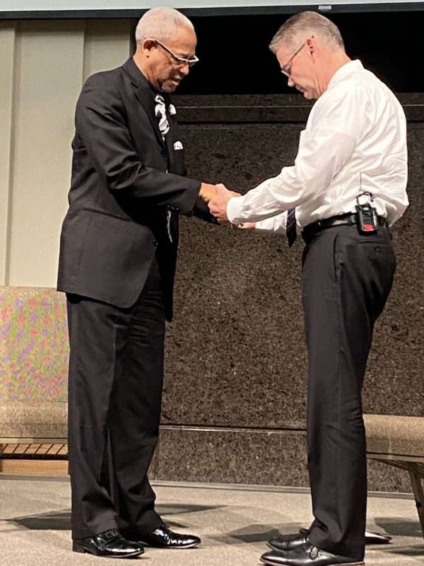 Ministers Tim Luster, left, and Tim Pyle pray at a joint assembly of their Tulsa-area congregations.