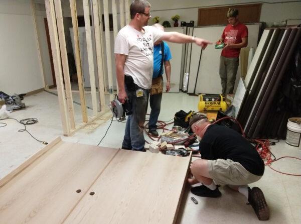 Volunteers from the Woodbury Church of Christ work on a project to renovate the Minneapolis Central Church of Christ's food pantry.