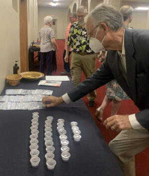Elder Ted Presley picks up communion elements — a Chiclet-style cracker in a plastic bag and grape juice in a tiny cup — at the University Church of Christ in Abilene, Texas.