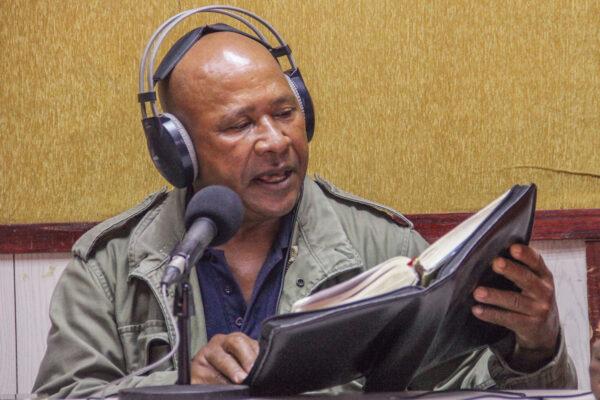 "At radio station UVA FM 97.3, Manuel Aquino reads Scripture during the ""Buena nueva por todos"" (""Good News for Everyone"") program."