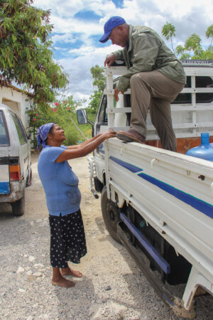 Manuel Aquino chats with one of his customers as he delivers water to the communities near Neyba.