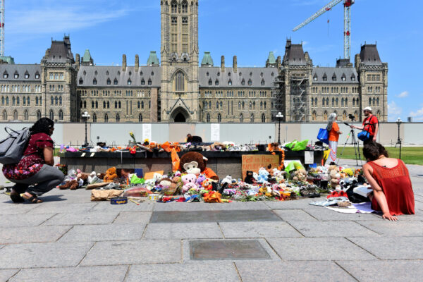 Canadians leave shoes and toys on Parliament Hill in Ottawa in memory of the 215 children whose remains were found in British Columbia.
