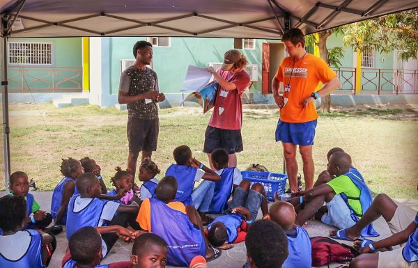 Members of the Clear Creek mission team tell Haitian children stories about Jesus.