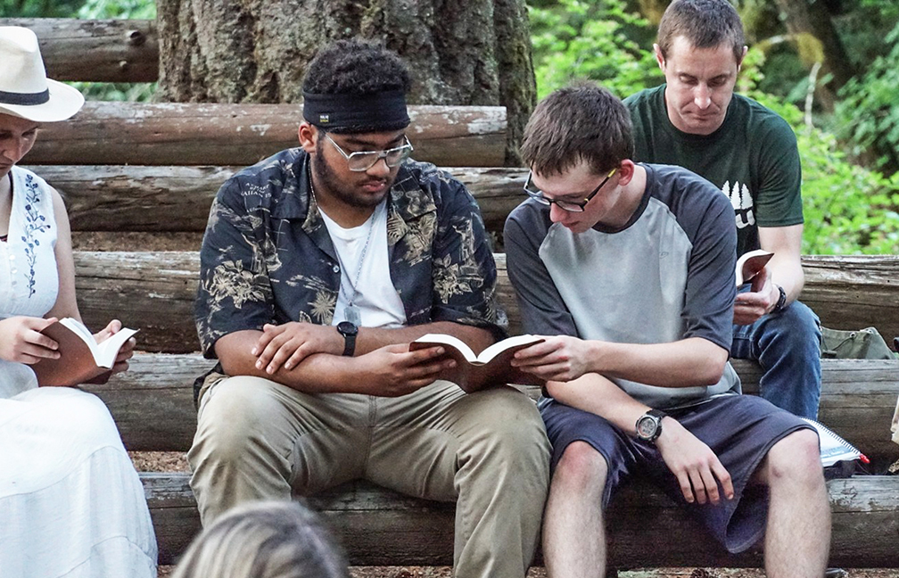 Two campers share a Bible as they follow along with a daily lesson.