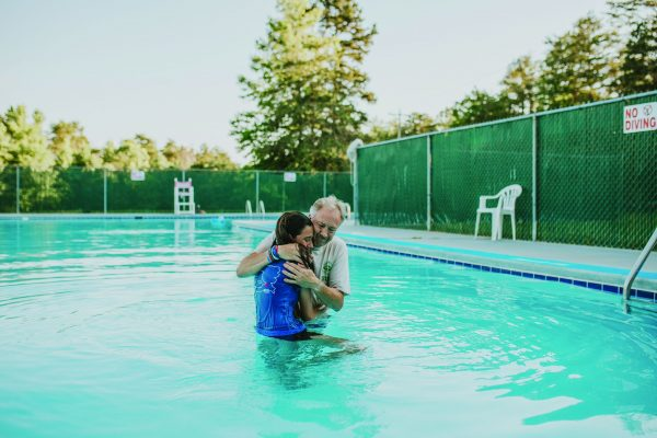 Jasmine Paz gets a hug from Kirk Sams, Carolina Bible Camp's longtime first-week camp director, after her baptism.