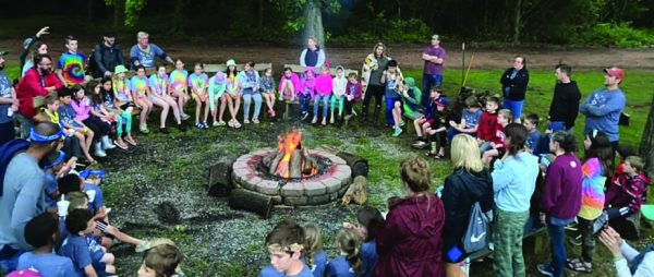Campers and counselors gather around a fire on the last night of Inside Out.
