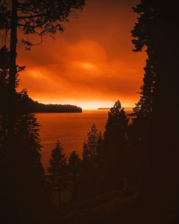 The Dixie Fire casts an orange glow over Lake Almanor on July 17.