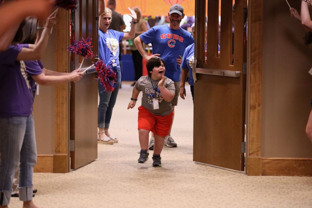Volunteers at the Highland Church of Christ in Cordova, Tenn., welcome Asher Honshell, center, to a recent Vacation Bible School for children and adults with disabilities.