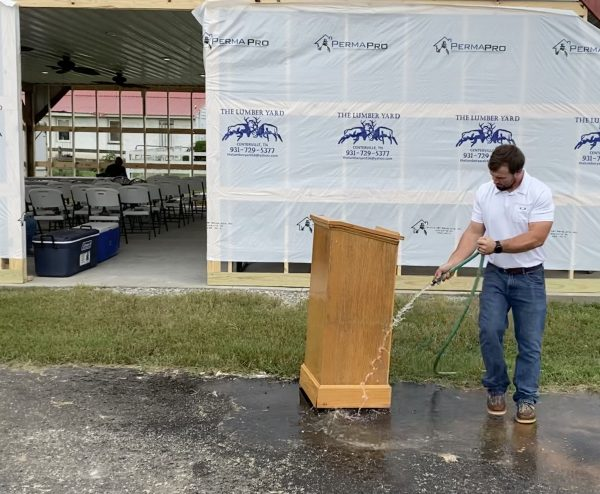Drew Grimes sprays the pulpit recovered from the flooded church.