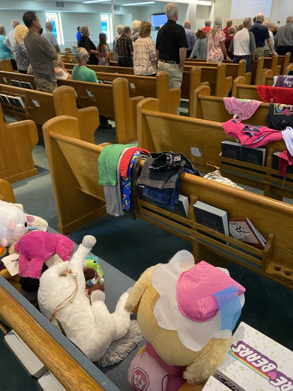Stuffed animals and clothing cover some of the pews in the Waverly Church of Christ auditorium in Tennessee.