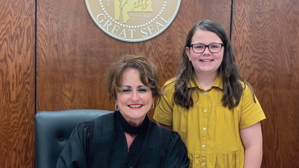 Judge Carole Coil Medley poses behind the bench with visitor Lizzie Crunk, a fellow member of the Killen Church of Christ in Alabama.
