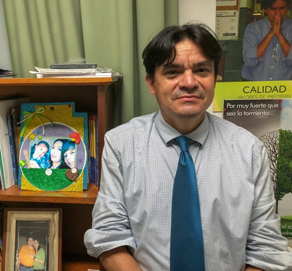 In his office at Predisan, Julio Benitez stands next to a photo of his wife and children. As the COVID-19 pandemic drags on in Honduras, the couple takes turns attending events with their congregation and teaches their children at home.