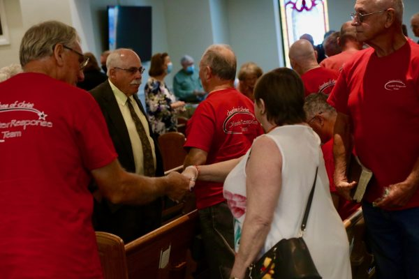 Members and disaster relief volunteers greet each other after Sunday morning worship at the Waverly Church of Christ.